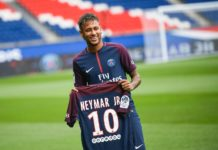 """TOPSHOT - Brazilian superstar Neymar poses with his new jersey during his official presentation at the Parc des Princes stadium on August 4, 2017 in Paris after agreeing a five-year contract following his world record 222 million euro ($260 million) transfer from Barcelona to Paris Saint Germain's (PSG). Paris Saint-Germain have signed Brazilian forward Neymar from Barcelona for a world-record transfer fee of 222 million euros (around $264 million), more than doubling the previous record. Neymar said he came to Paris Saint-Germain for a """"bigger challenge"""" in his first public comments since arriving in the French capital. / AFP PHOTO / Lionel BONAVENTURE"""