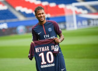 "TOPSHOT - Brazilian superstar Neymar poses with his new jersey during his official presentation at the Parc des Princes stadium on August 4, 2017 in Paris after agreeing a five-year contract following his world record 222 million euro ($260 million) transfer from Barcelona to Paris Saint Germain's (PSG). Paris Saint-Germain have signed Brazilian forward Neymar from Barcelona for a world-record transfer fee of 222 million euros (around $264 million), more than doubling the previous record. Neymar said he came to Paris Saint-Germain for a ""bigger challenge"" in his first public comments since arriving in the French capital. / AFP PHOTO / Lionel BONAVENTURE"