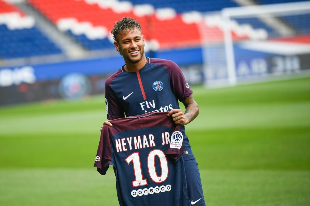 TOPSHOT - Brazilian superstar Neymar poses with his new jersey during his official presentation at the Parc des Princes stadium on August 4, 2017 in Paris after agreeing a five-year contract following his world record 222 million euro ($260 million) transfer from Barcelona to Paris Saint Germain's (PSG). Paris Saint-Germain have signed Brazilian forward Neymar from Barcelona for a world-record transfer fee of 222 million euros (around $264 million), more than doubling the previous record. Neymar said he came to Paris Saint-Germain for a